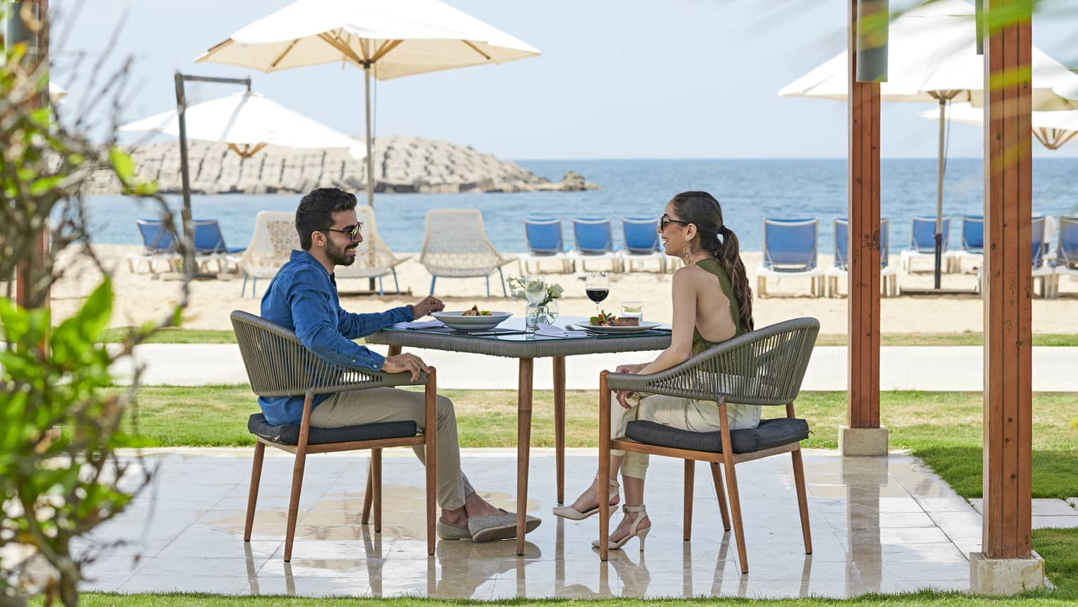 A couple dines outdoors at a table overlooking the beach at four seasons alexandria
