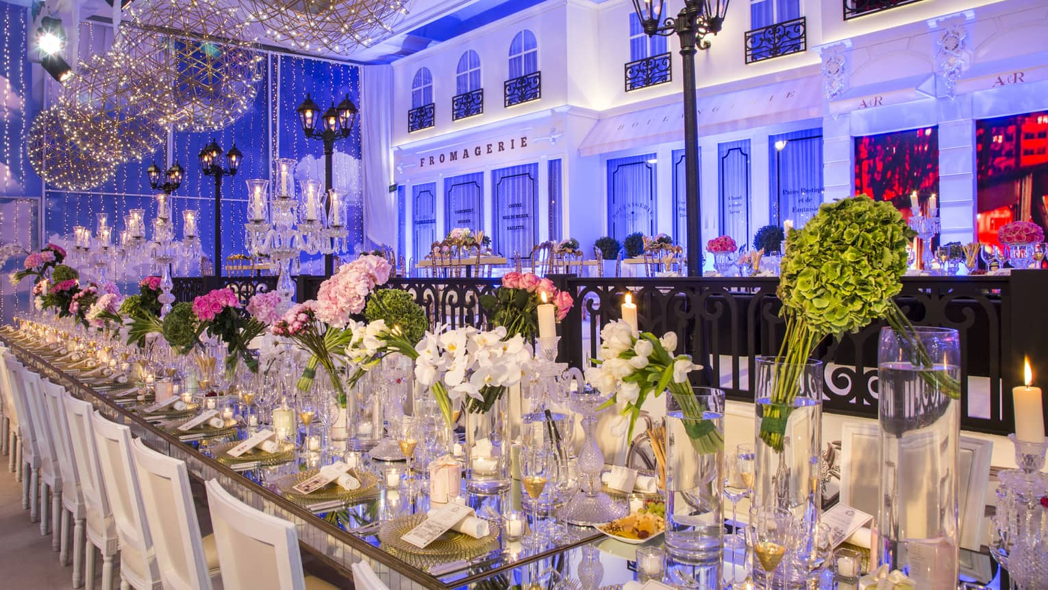 Long banquet dining table with white orchids, pink flowers under modern lights, Paris accent wall with blue lights