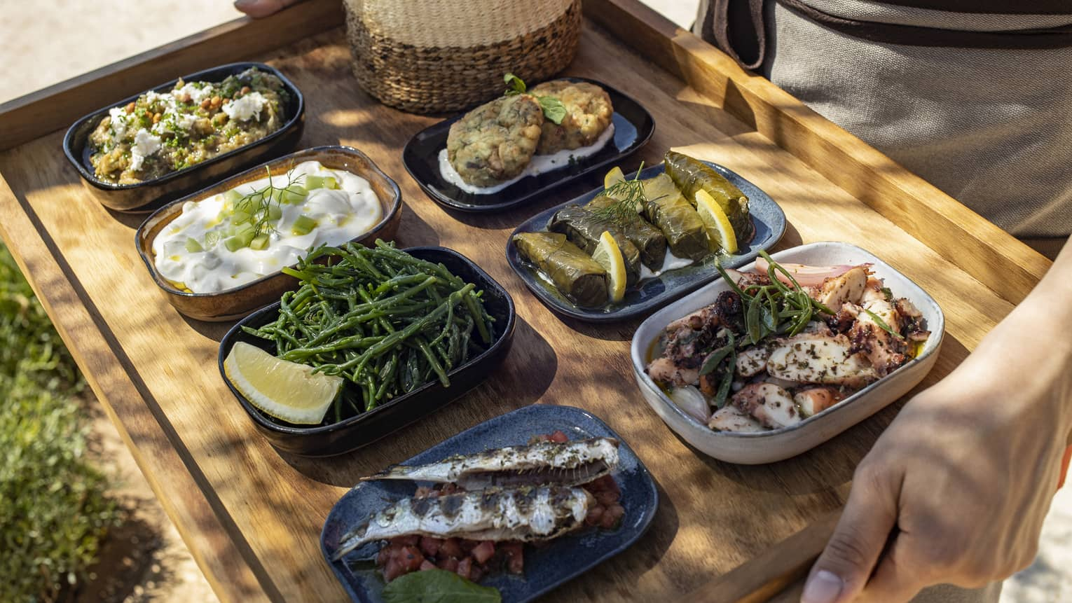 Seven shareable Greek dishes carried on wooden tray outdoors