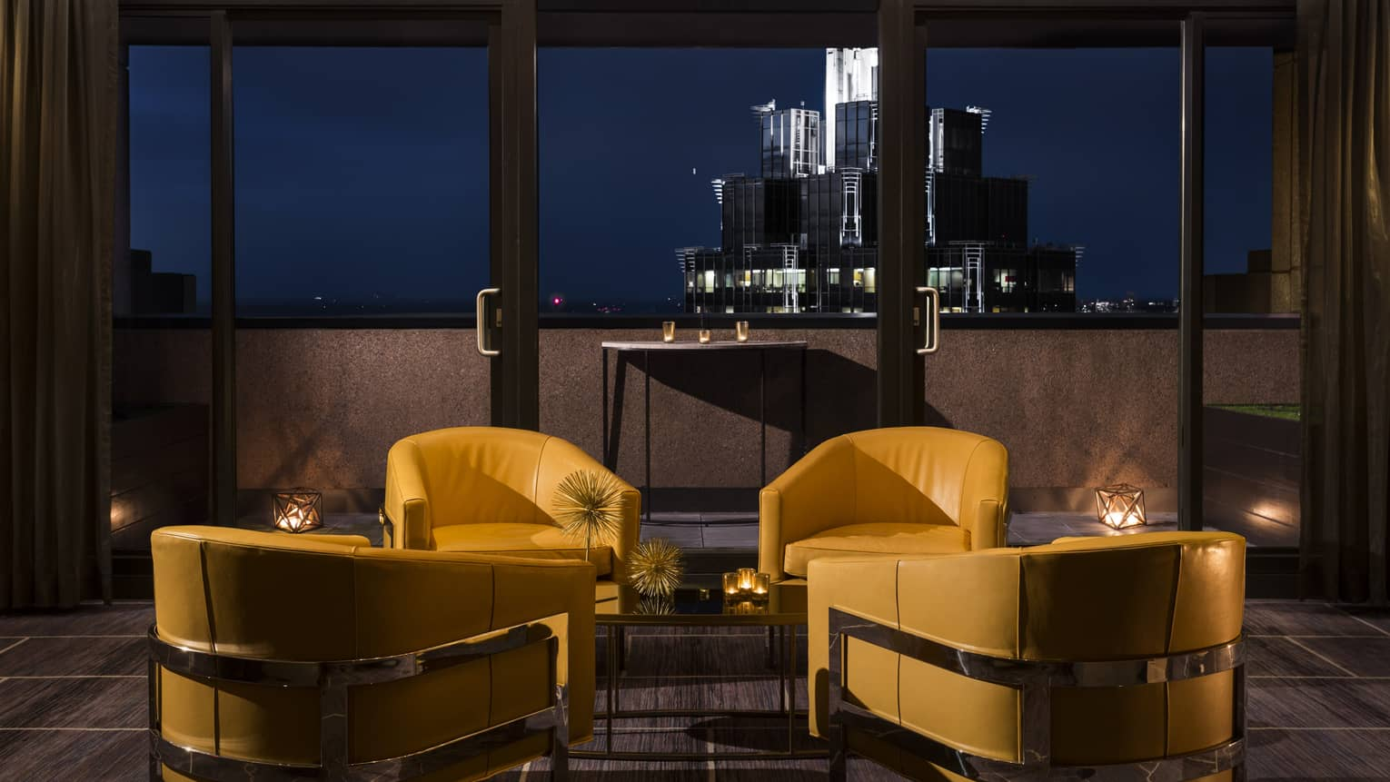 Yellow leather lounge chairs at dusk, the cityscape in the background