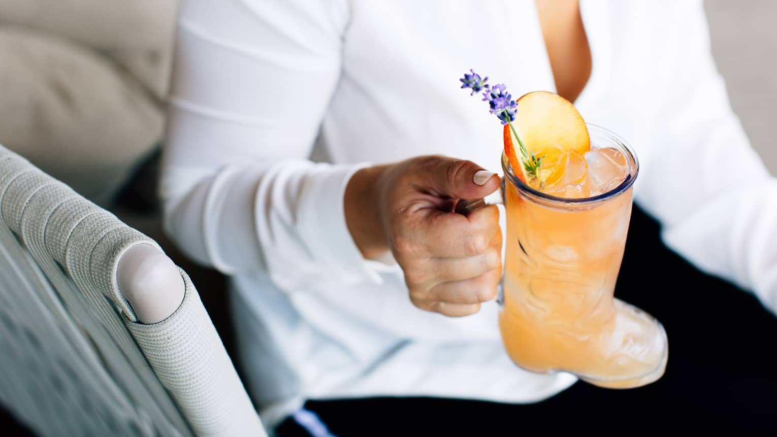 A close up of a woman's hand holding a Honey Bee-Vo Cocktail garnished with an apple slice and sprig of lavendar