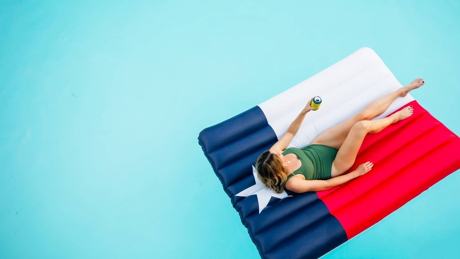 a woman lounges in a pool on a float that looks like the texas state flag