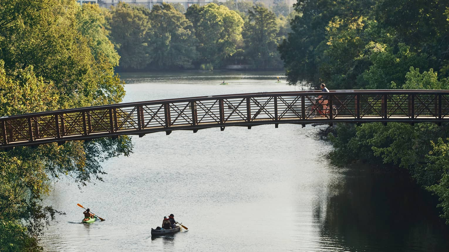 People in kayak, canoe on lake under cyclist on foot bridge