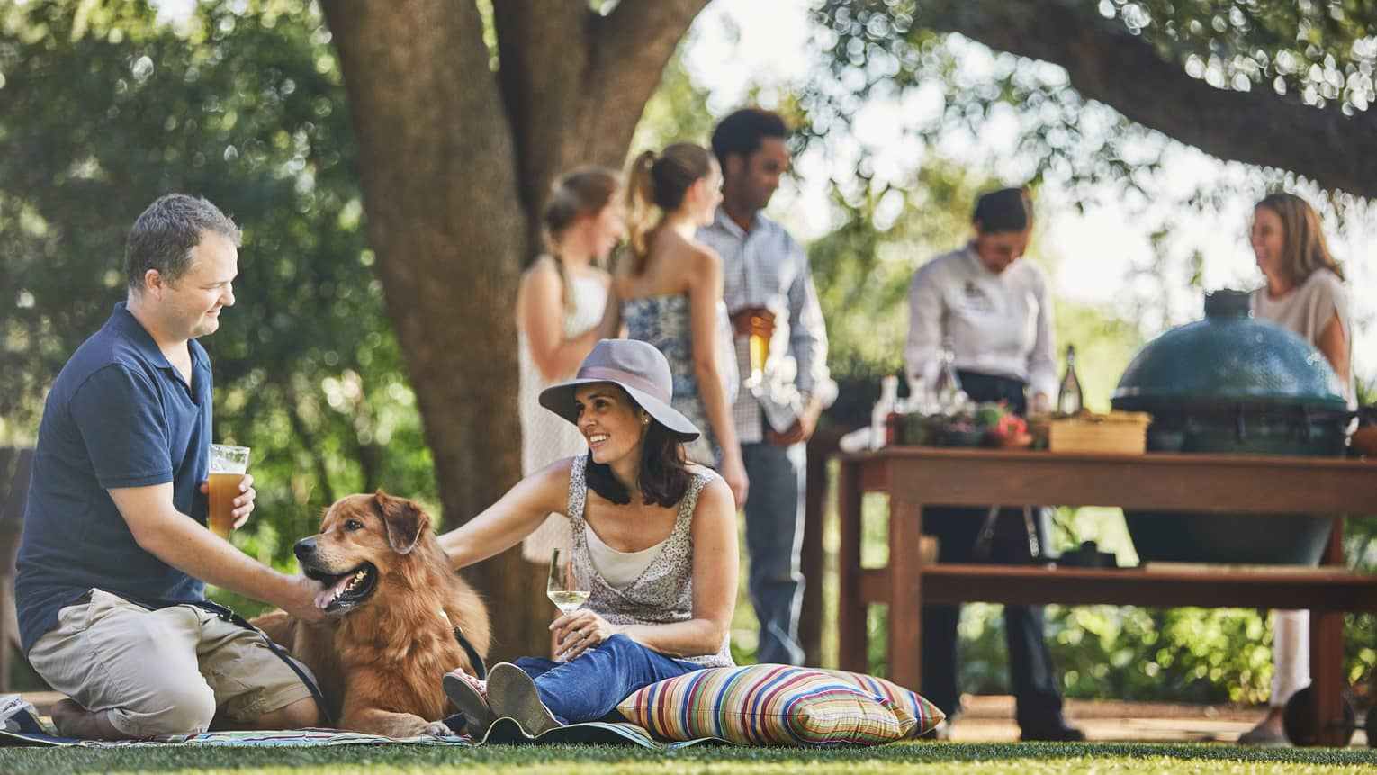 Man with beer, woman with wine sit on lawn, pet large dog, people around barbecue in background