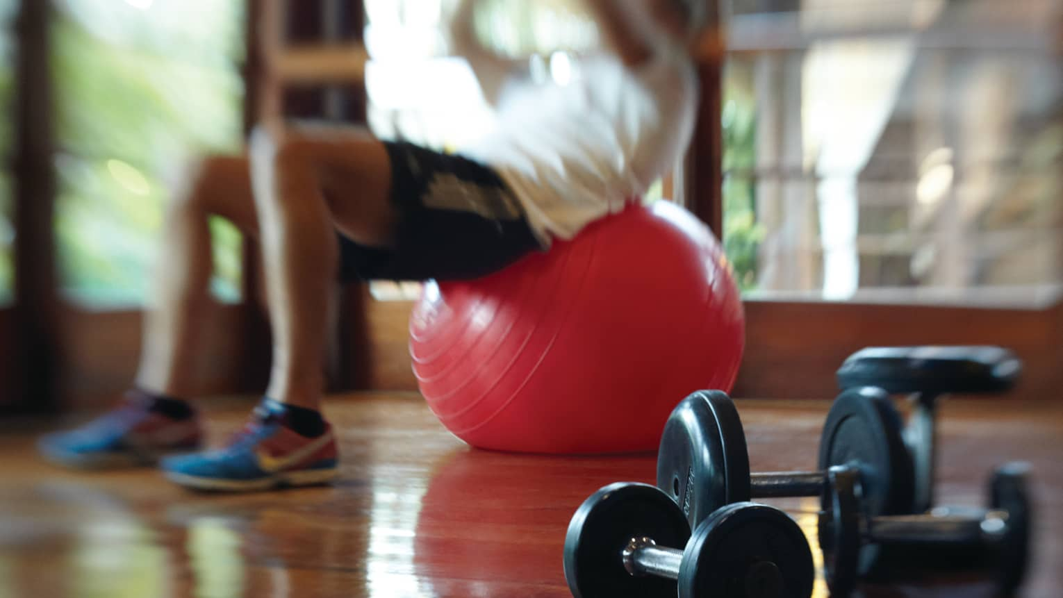 Blurry image of man in exercise clothes balancing his back on red pilates ball in Fitness Centre