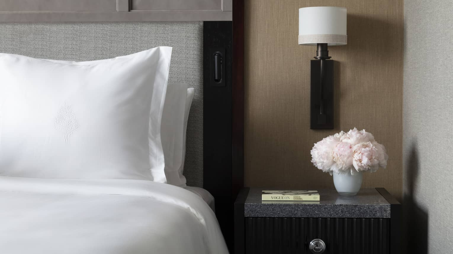 Sleek bedside table next to a crisp white Four Seasons bed