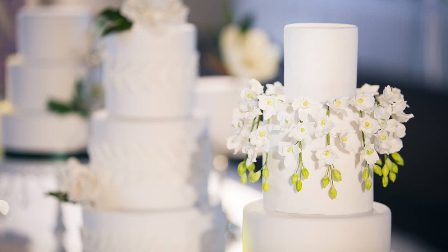Three-tiered wedding cakes are each garnished with white florals