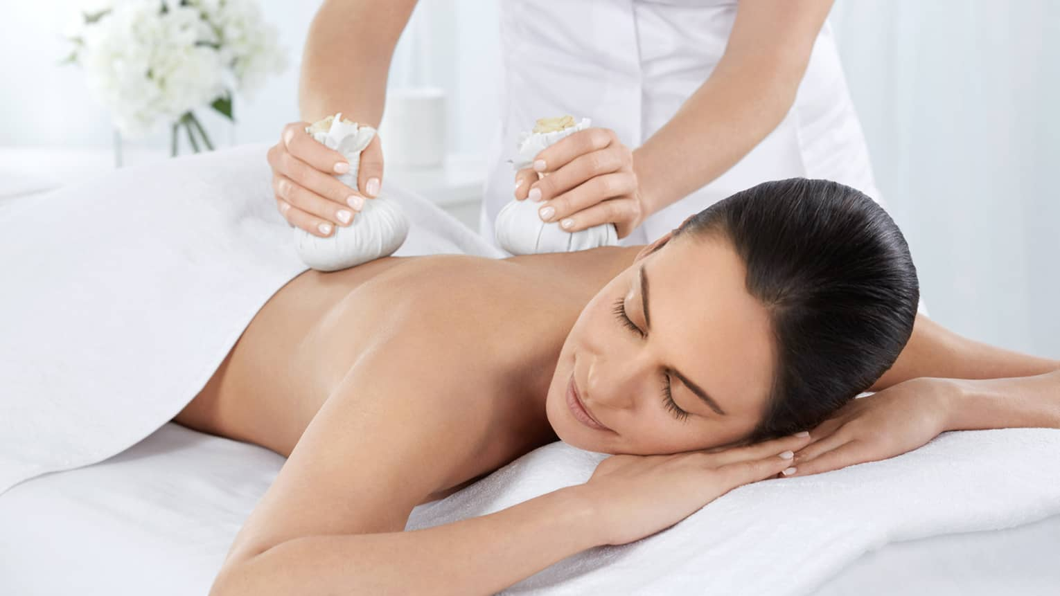 Woman with eyes closed lies under white sheet on massage table, staff presses herbs on shoulders