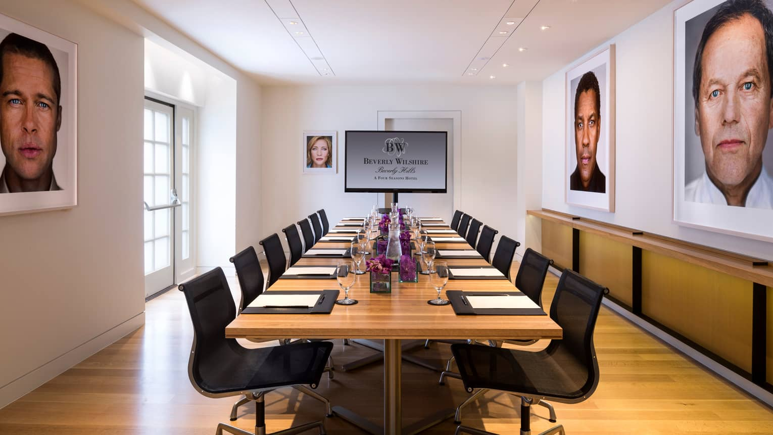 Petit Cut long meeting table, TV screen at end, framed prints of Hollywood stars
