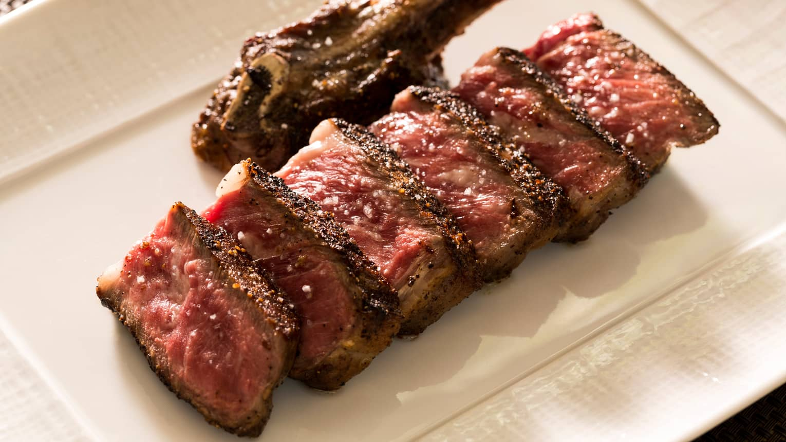 Japanese Pure Wagyu Beef slices of sirloin steak on white platter
