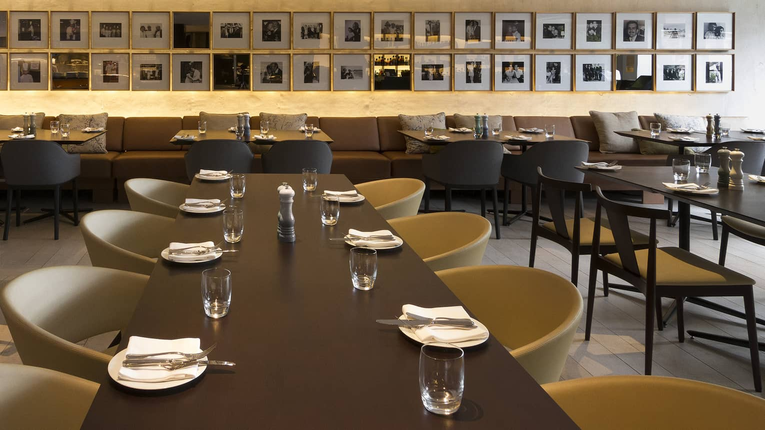 Black and white photographs line the wall, tables are arranged with white napkins
