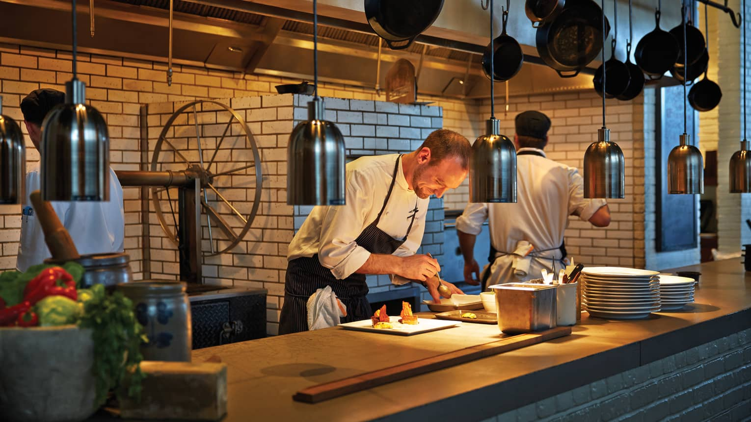 Chef garnishes dishes on brick restaurant line with hanging lamps