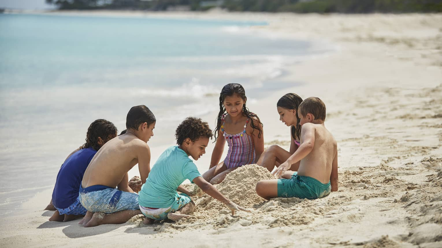 A group of children plays in the sand together on the beach