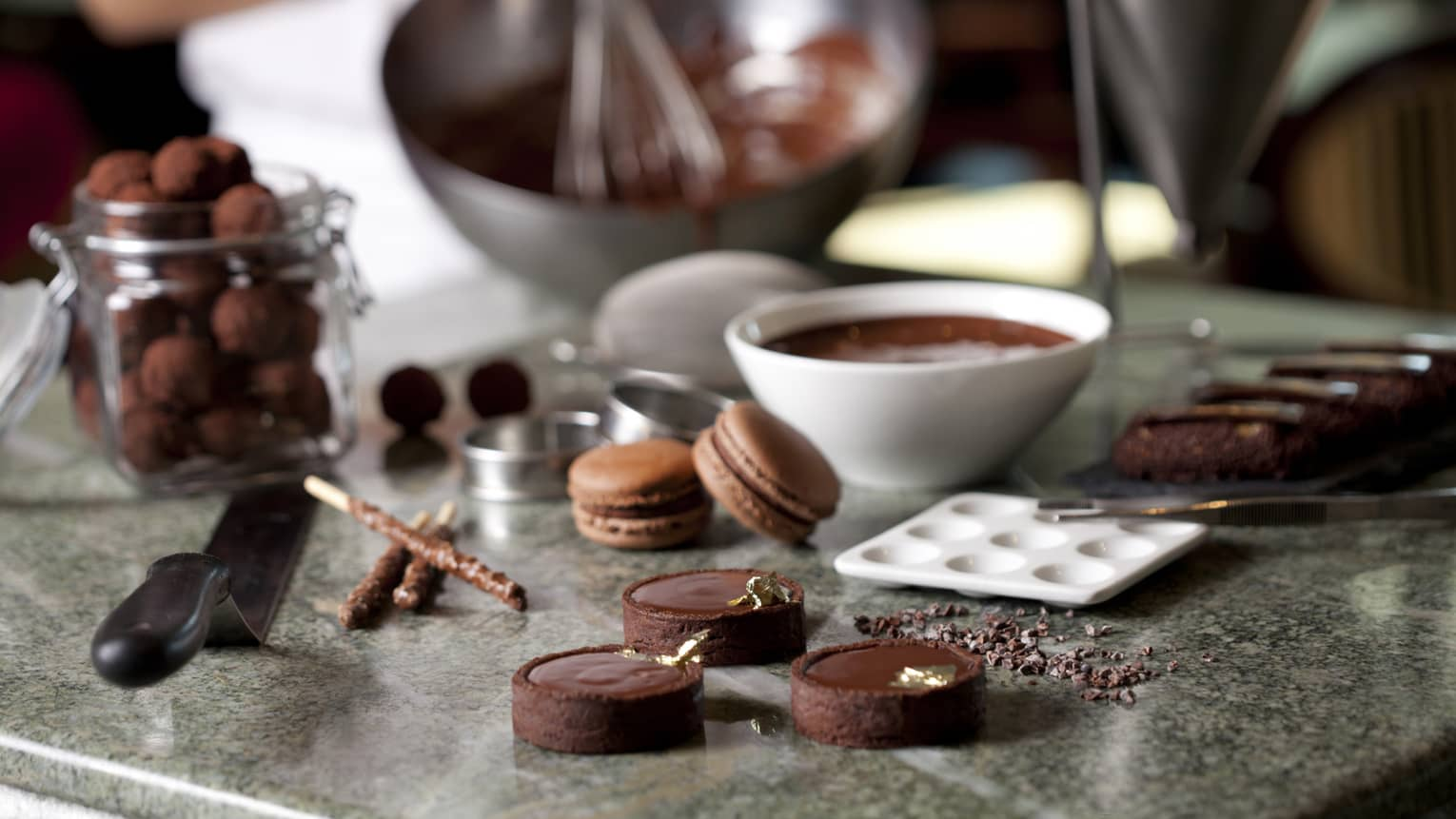 Close-up of fine chocolates, macarons, bowl of melted chocolate on counter