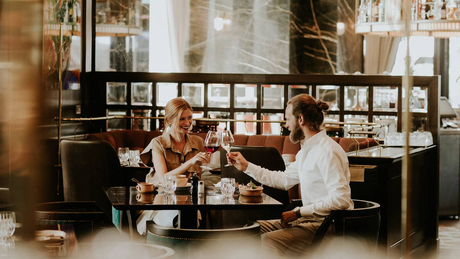 Smiling couple at table toasts with wine glasses in restaurant lounge