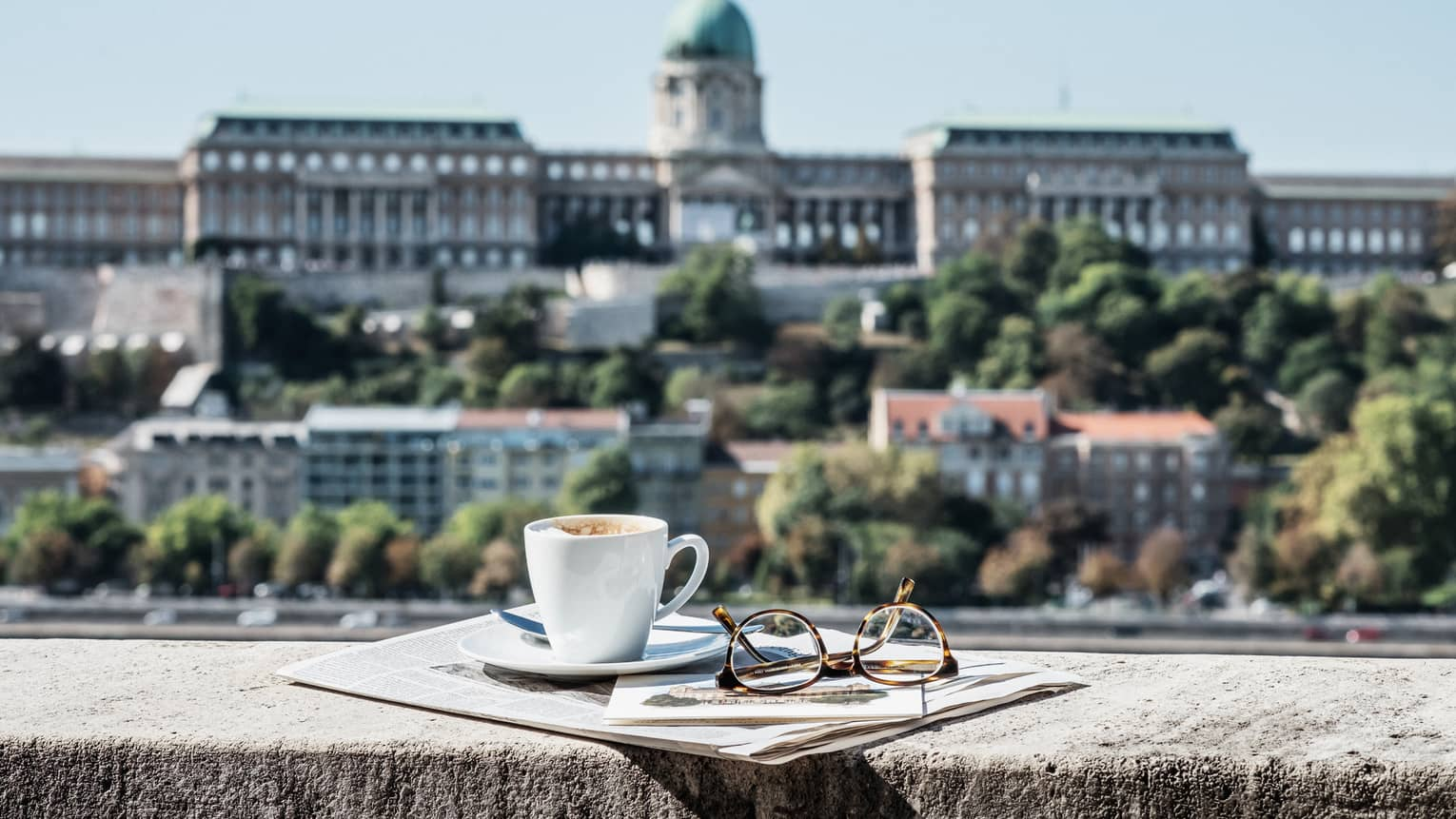 Morning view of Buda Castle from guest room terrace, cup of coffee, eyeglasses on rail
