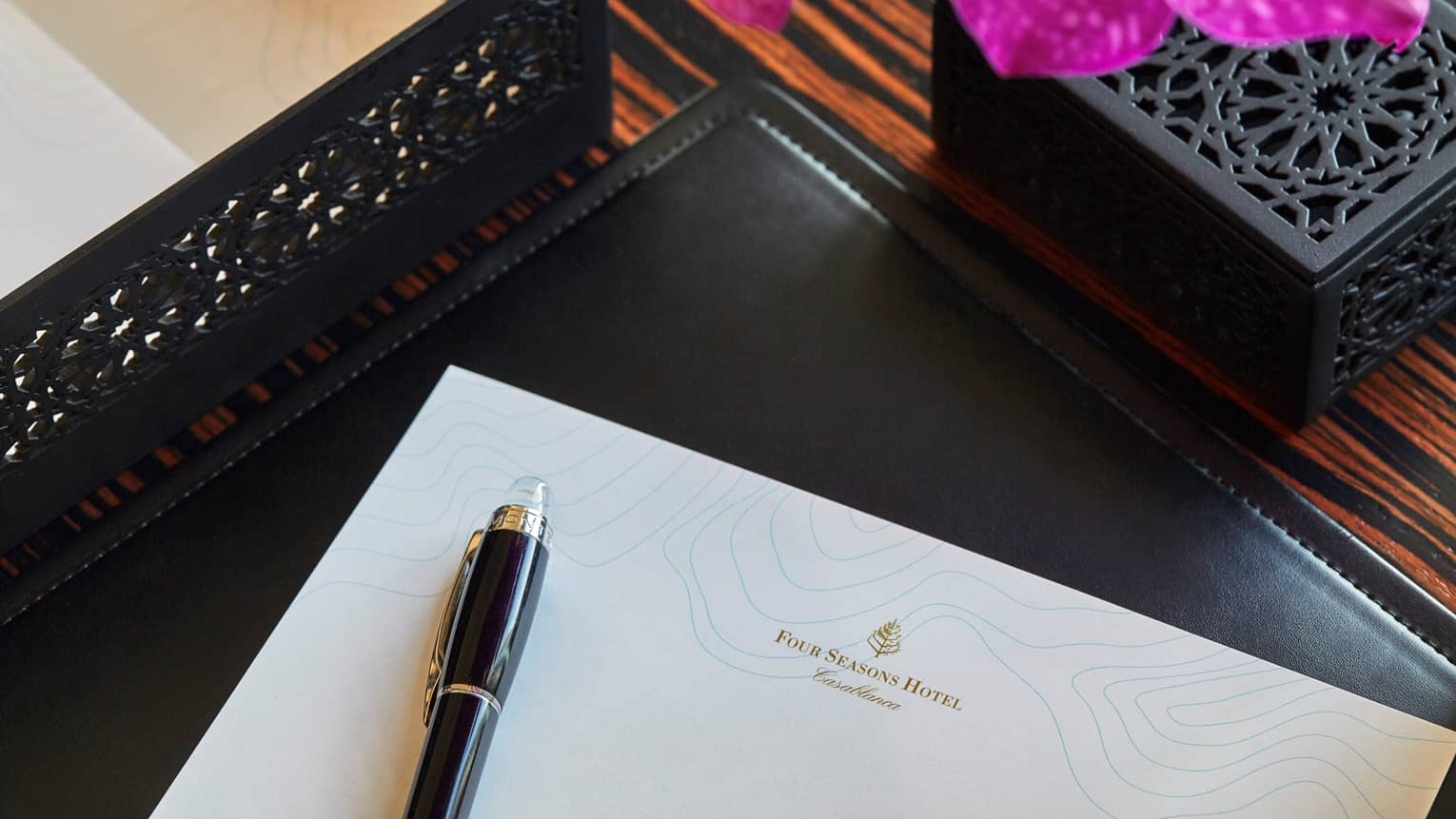 Corner of white piece of paper with Four Seasons logo, pen