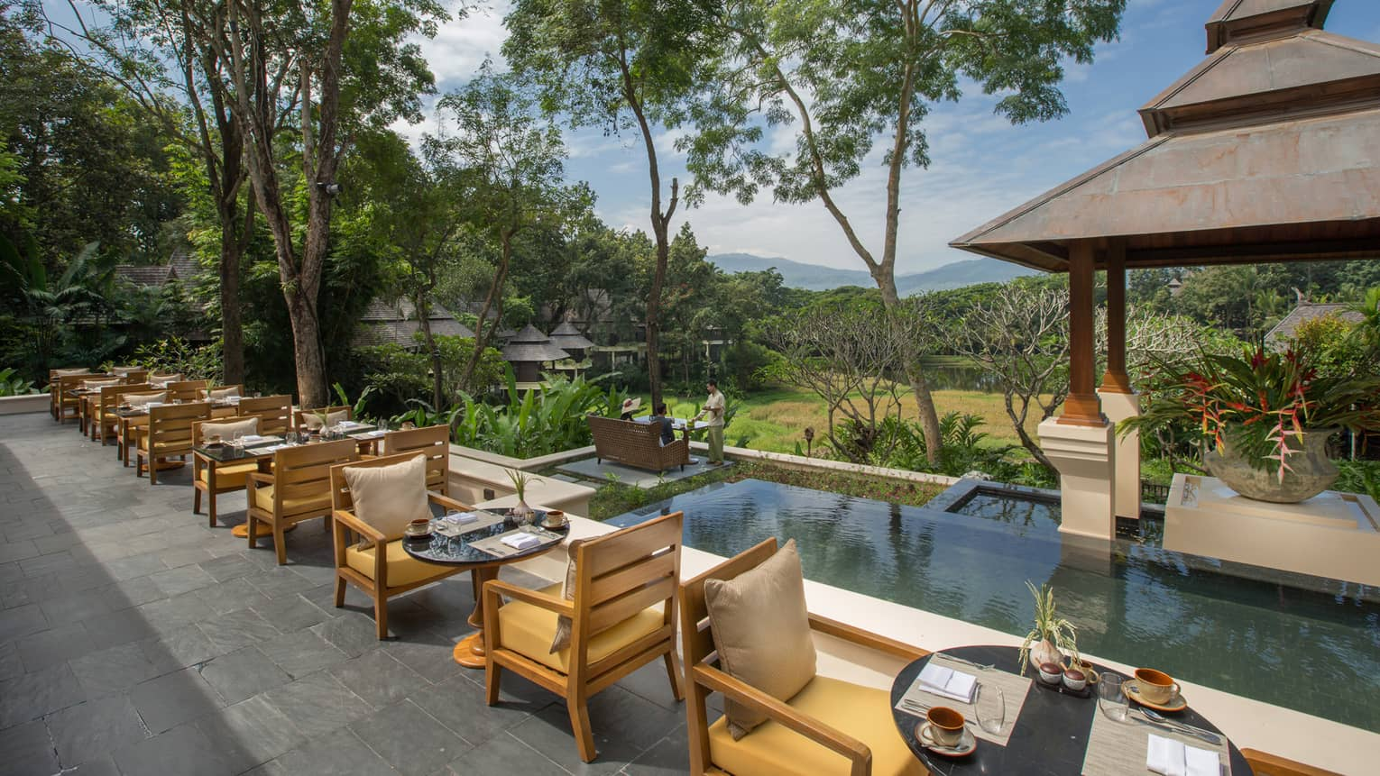 Outdoor terrace with dining tables, each with two wooden arm chairs, overlooking pool