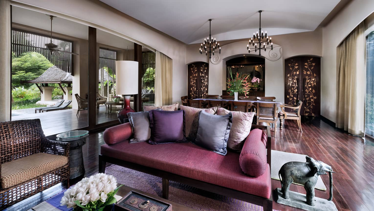 Family Residence living room with purple loveseat, accent pillows, elephant statue in front of dining room