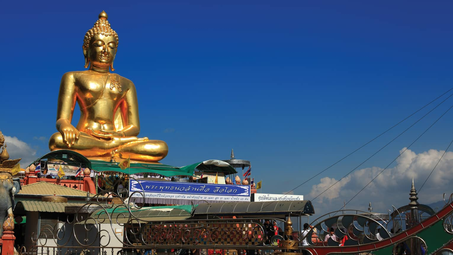 Gold Buddha statue on temple roof against a blue sky