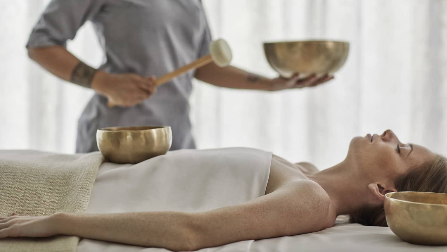 Woman with eyes closed lies on massage table as staff performs a treatment