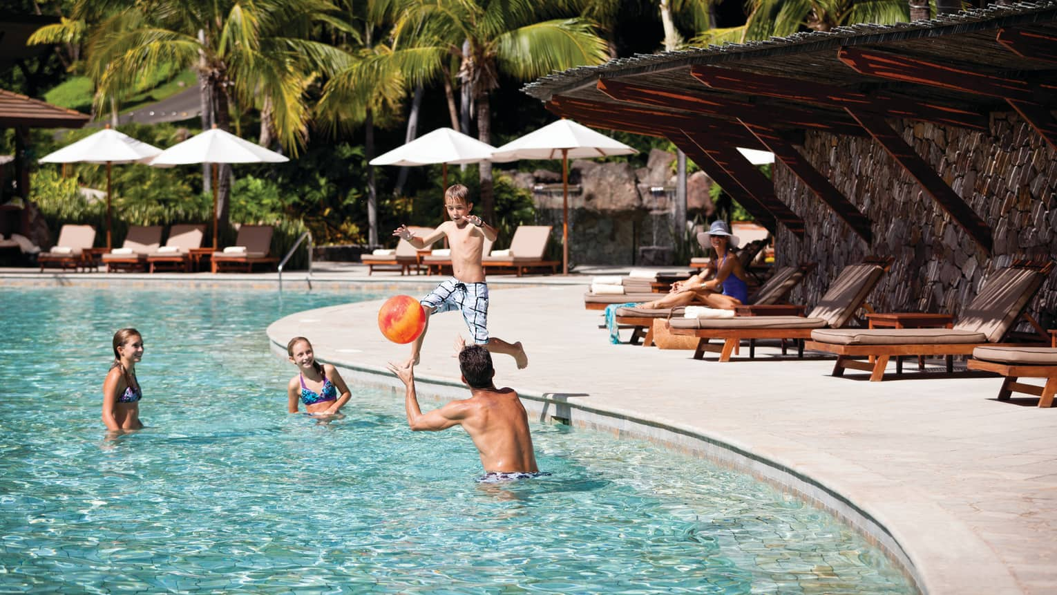 Boy jumps into outdoor Blanca swimming pool where family plays with orange beach ball