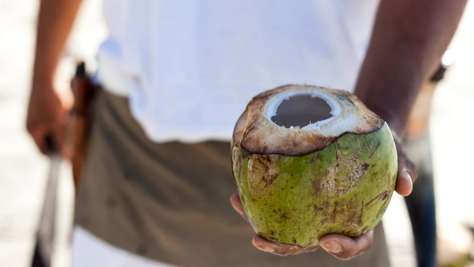 Close-up of man holding coconut with hole in top
