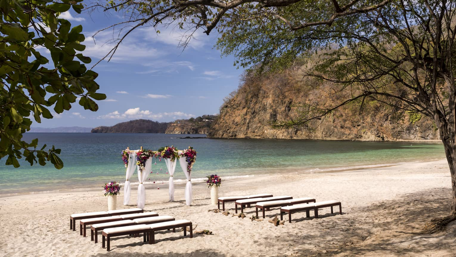 Rows of benches leading to wedding altar with white curtains, flowers on sand beach