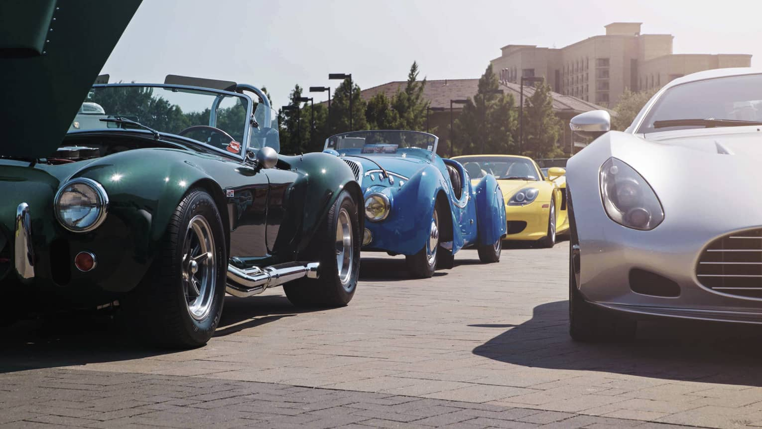 Green, blue, yellow and white luxury sports cars parked along road on sunny day, Four Seasons hotel in background
