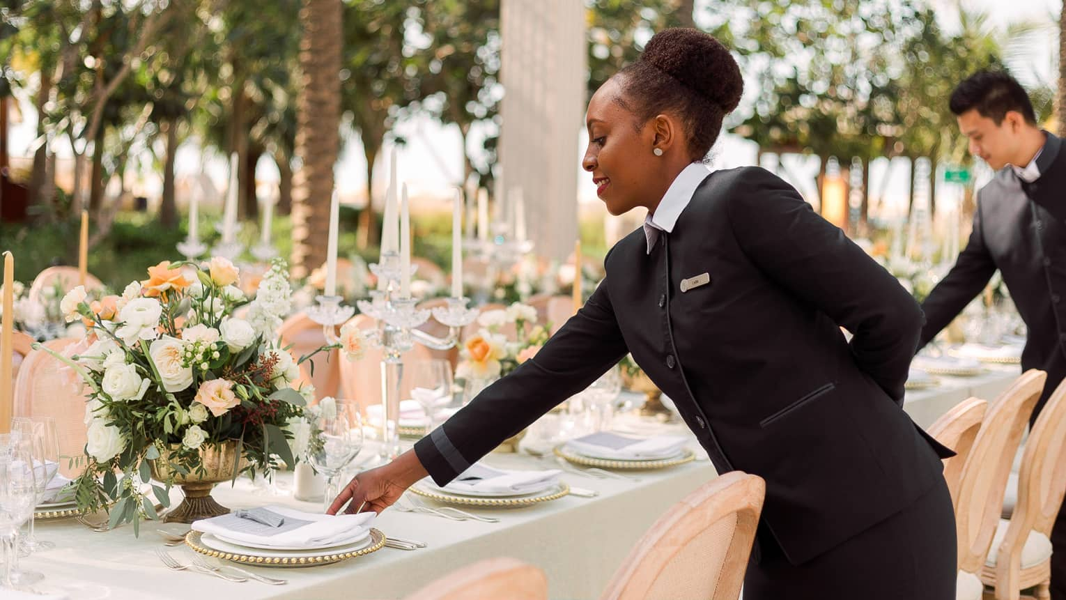 Hotel staff set plates on long banquet table at outdoor wedding reception