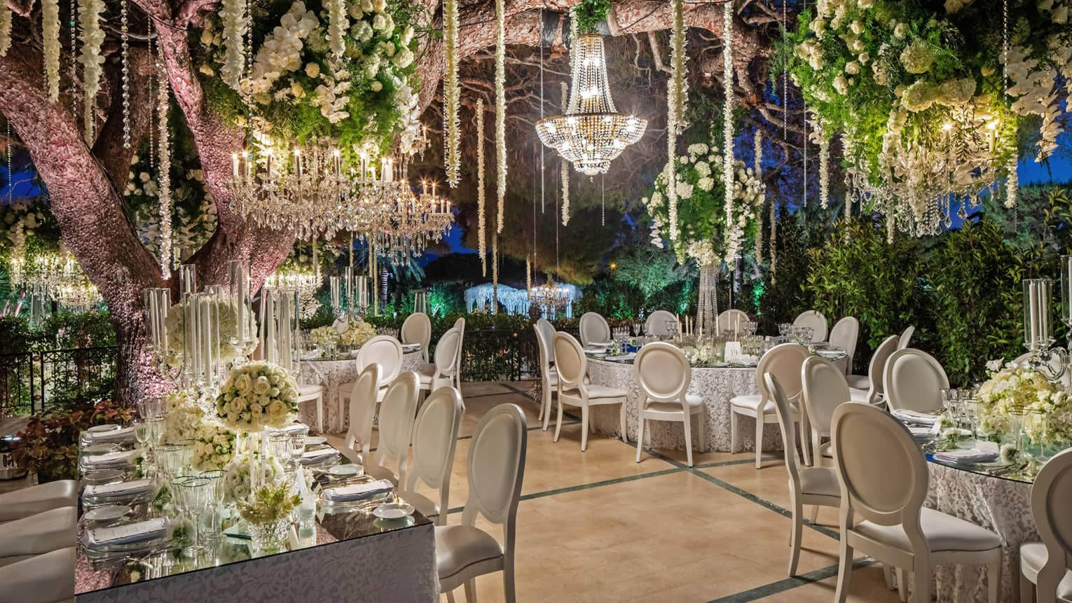 Four elegantly set mirrored-top tables with white chairs, crystal chandelier, floral arrangements hanging from ceiling