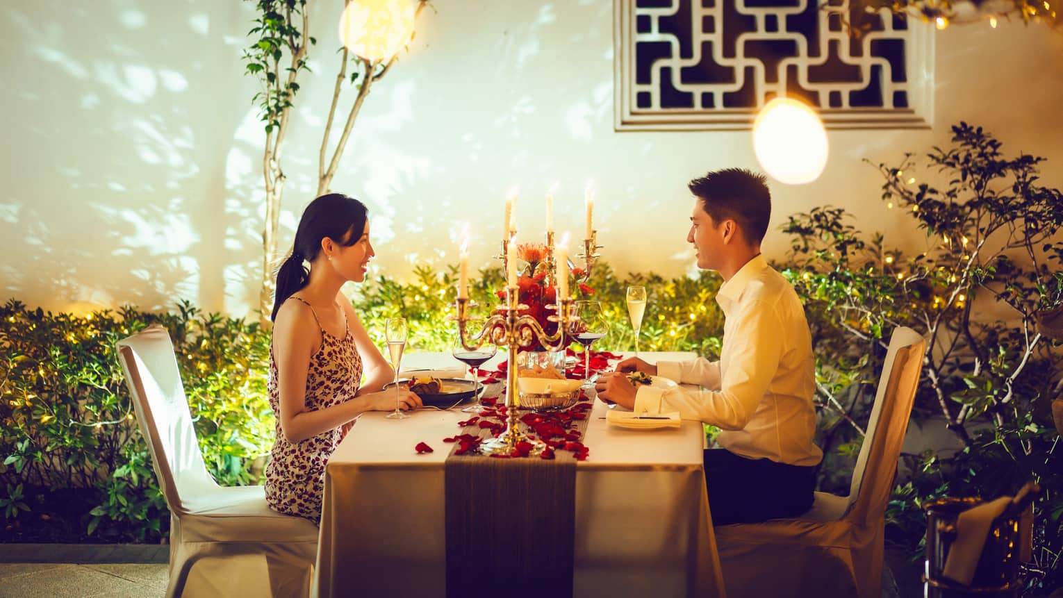 Couple at candle-lit private dining table with red rose petals on villa patio