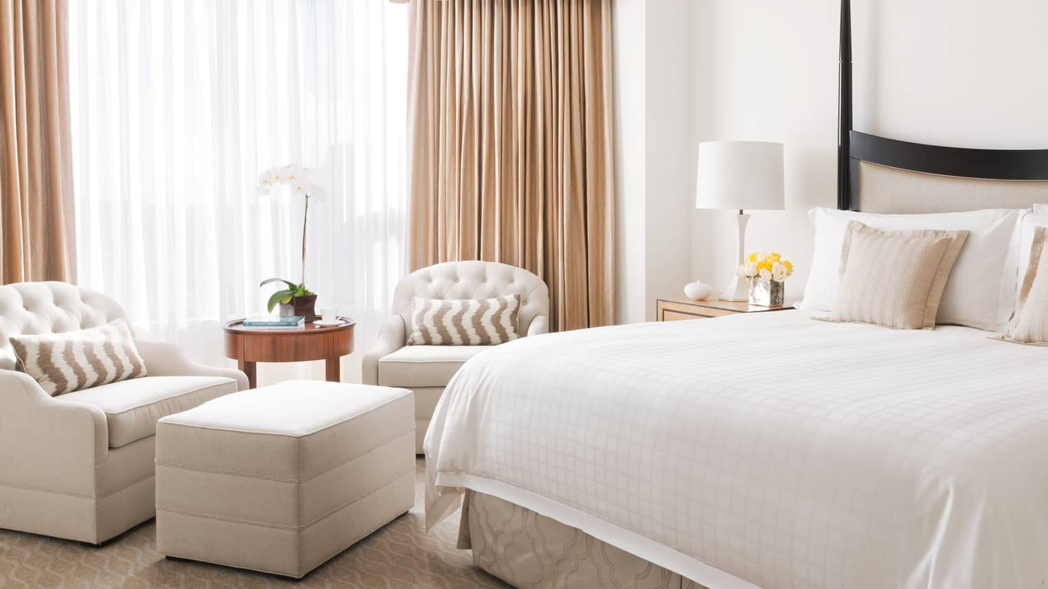 The light pours in from the windows in a neutral four seasons guest room furnishes with two cream arm chairs, a natural round wooden table, a black wooden bed and white linens