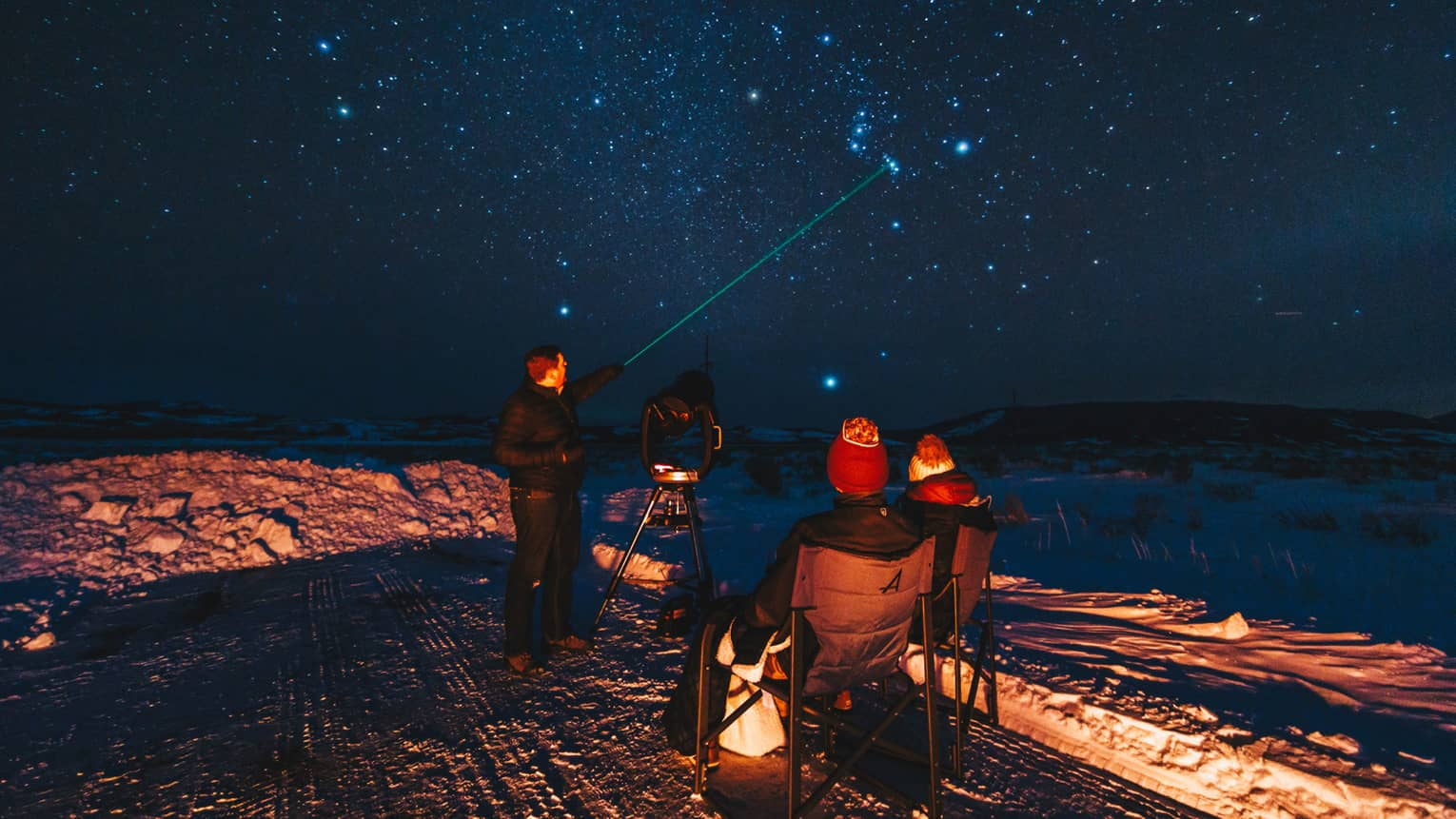 An instructor uses a laser pointer as he identifies constellations for guests