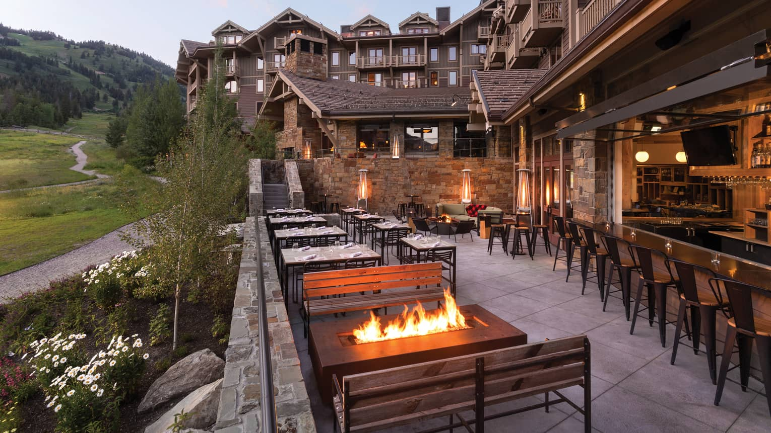 Handle Bar dining patio at dusk, outdoor fireplaces, mountains and lodge in background