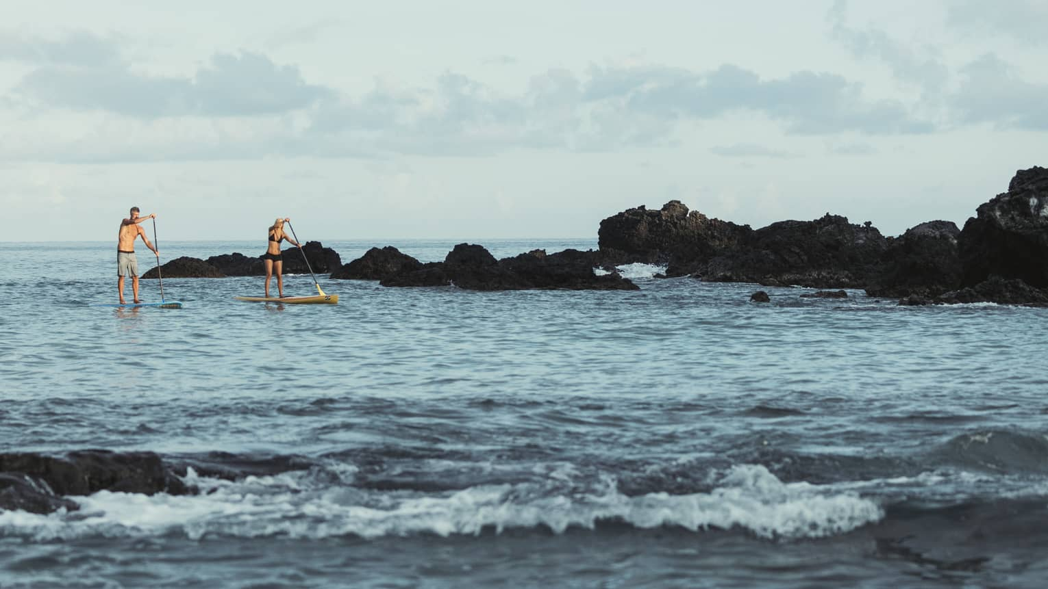 Two people balance on stand-up paddleboards in lagoon by black rocks