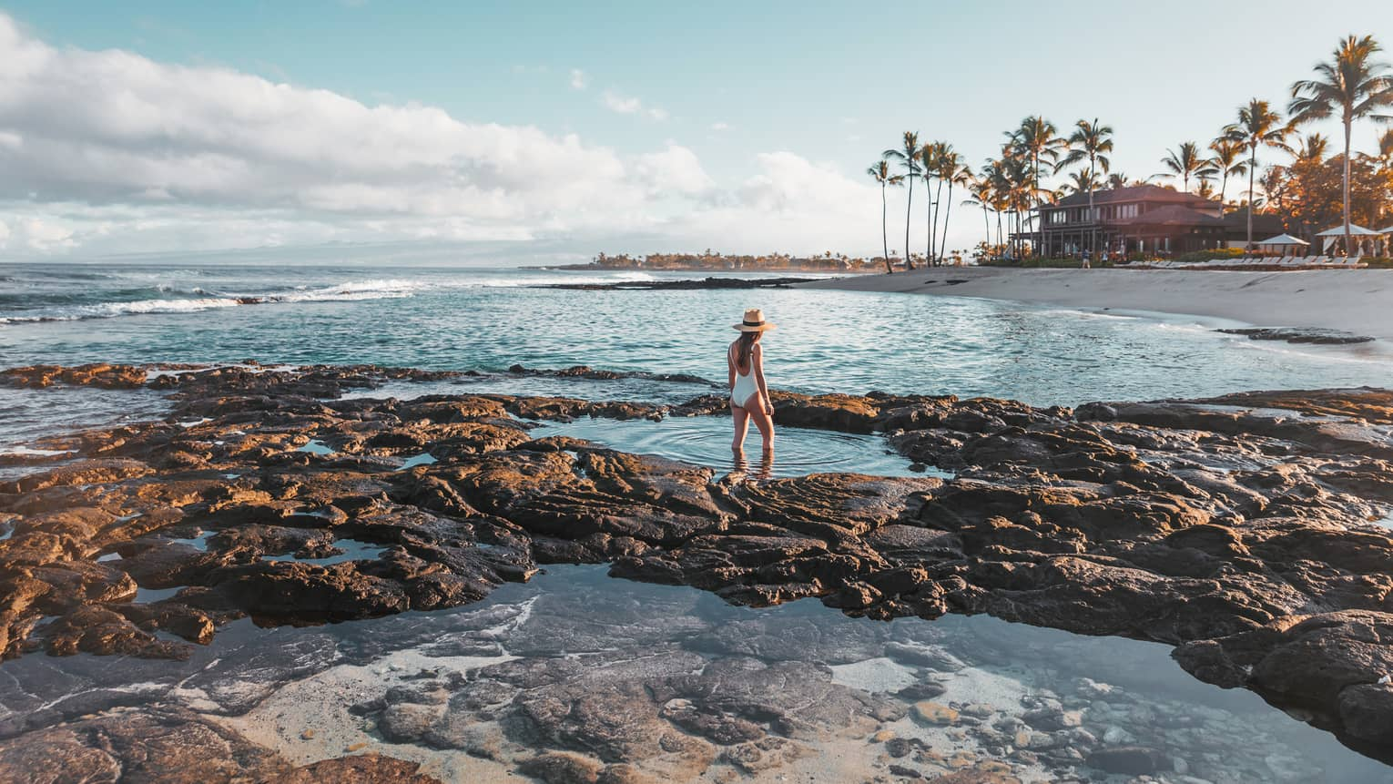 A guest exploring tidal pools by the beach in Hualalai