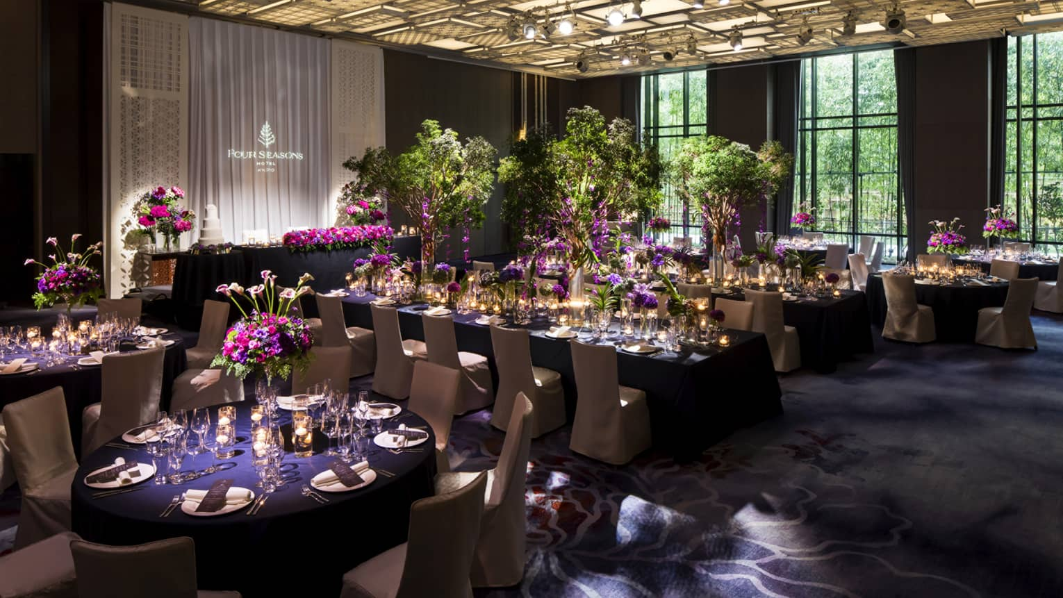 Wedding reception banquet, tables set with purple linens and flowers, under modern ceiling with lights