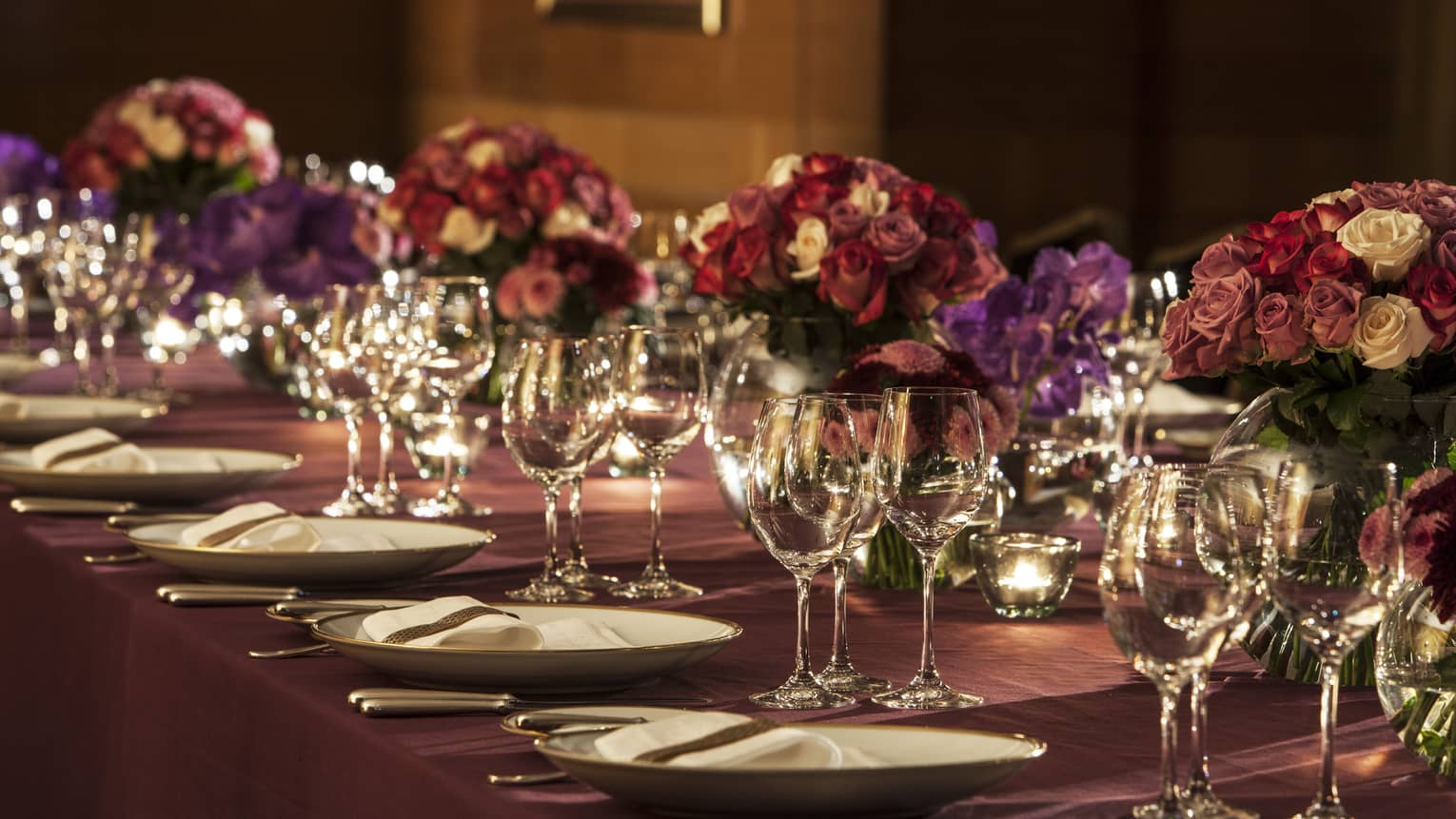 Deep pink and purple roses, wine glasses on elegant, candle-lit banquet table