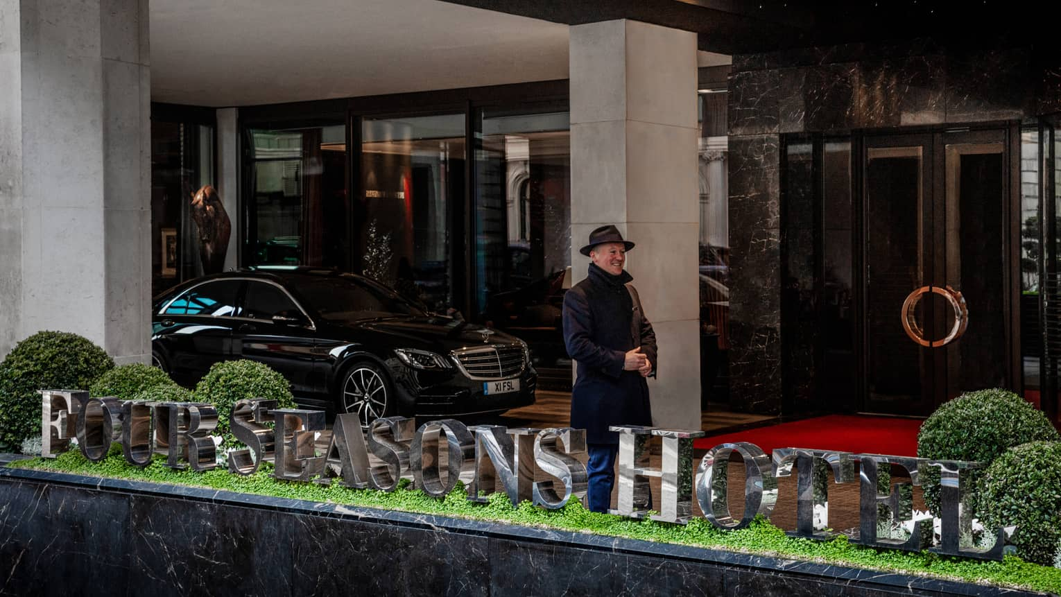 Man in dark winter coat and fedora, standing and smiling at hotel exterior under breezeway near black sedan and behind hotel sign