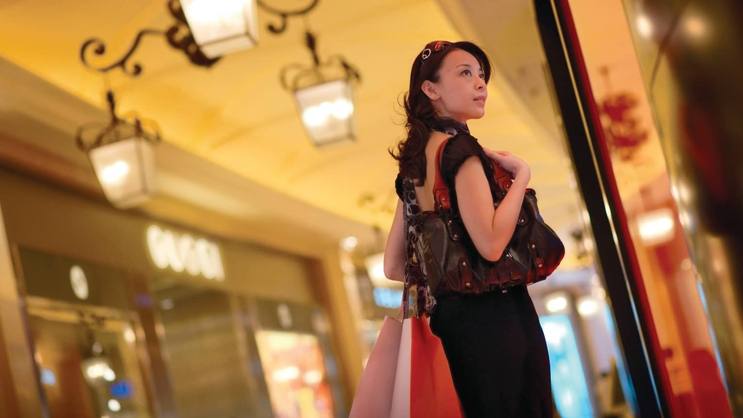 Fashionably-dressed woman carrying bags, designer purse in shopping mall