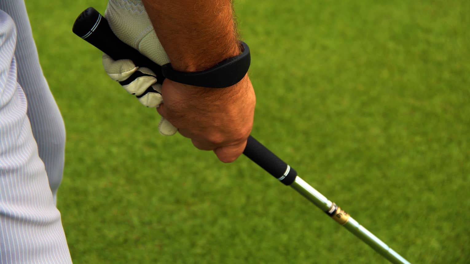 Close-up of hands gripping golf club on golf course green