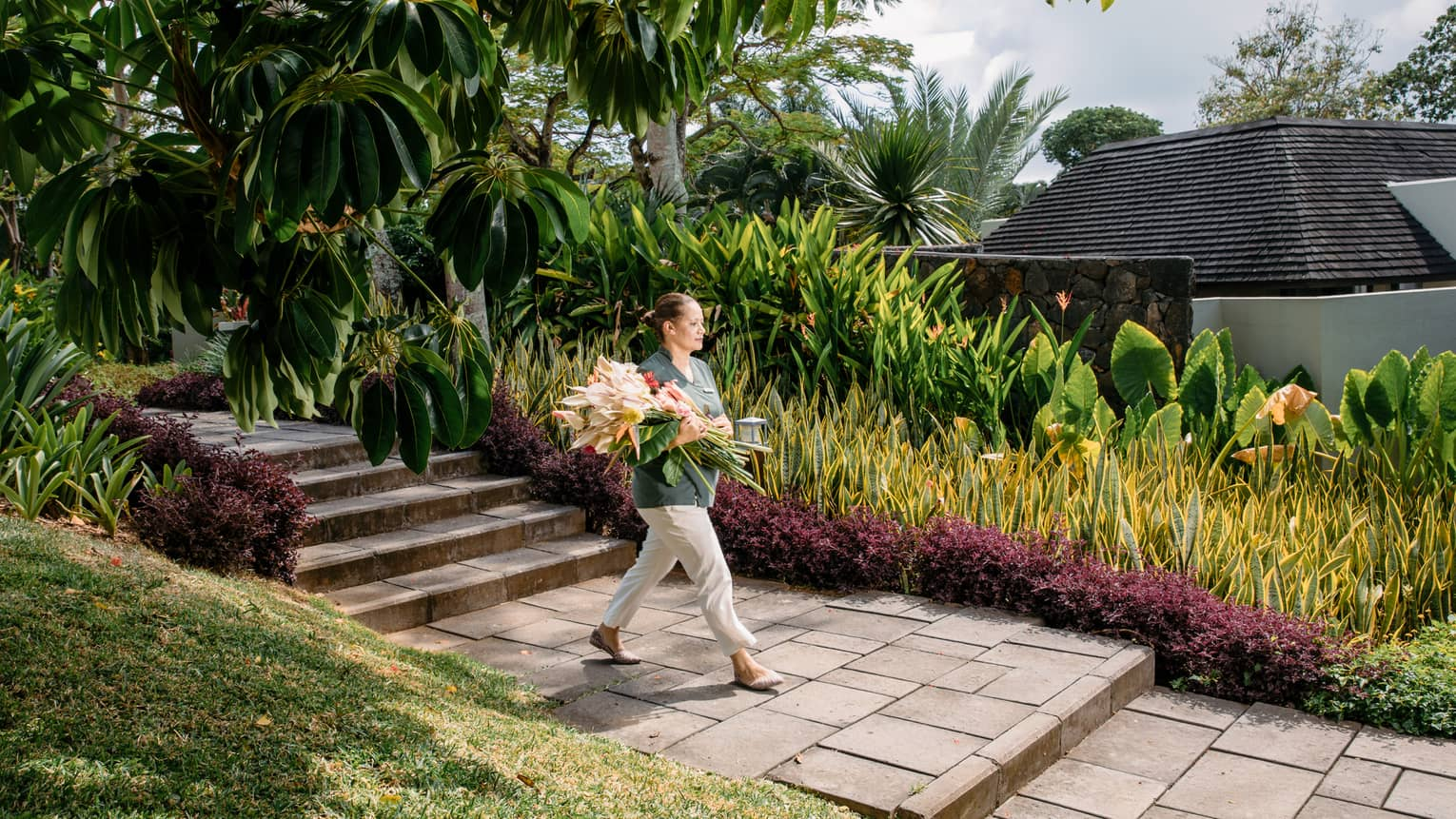 Hotel staff carries large bouquet of tropical flowers down brick path in garden