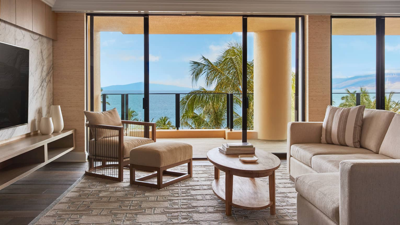Elite Suite sitting area with doors leading out to a private terrace and a view onto the ocean