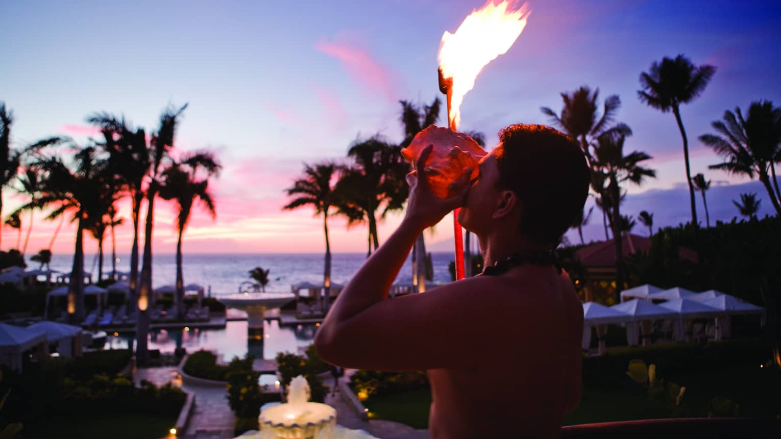 A staff member lights a torch with a view of the ocean