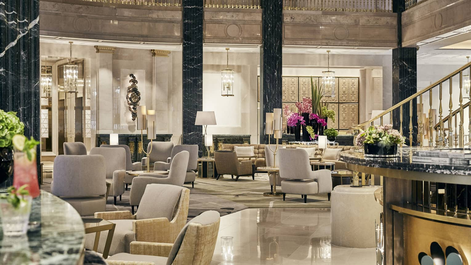 2-story columned lobby with marble flooring, gold accents and leather chairs