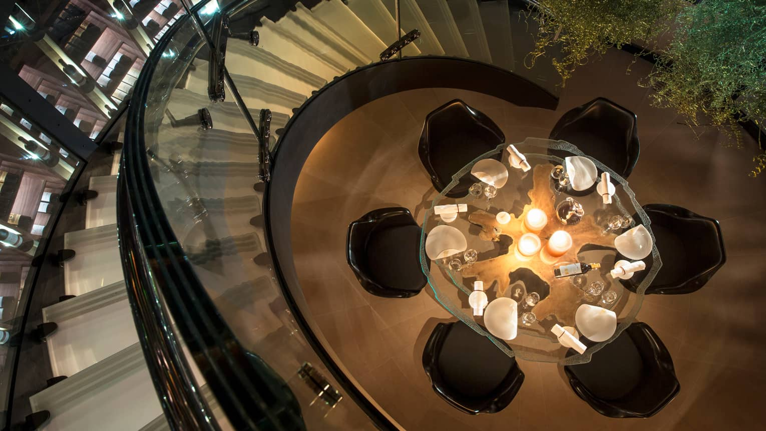 Aerial view of round glass candle-lit dining table, chairs from spiral staircase