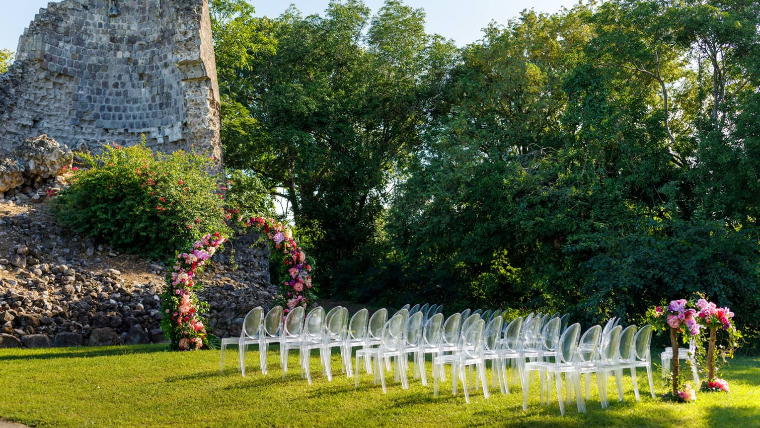 Outdoor wedding setup at Tea Mill rock structure, lucite chair grouping, flowers, flanked by bushes