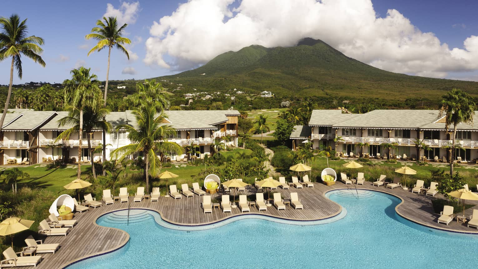 Aerial view of Four Seasons Resort Nevis white sand beach, buildings, green mountain