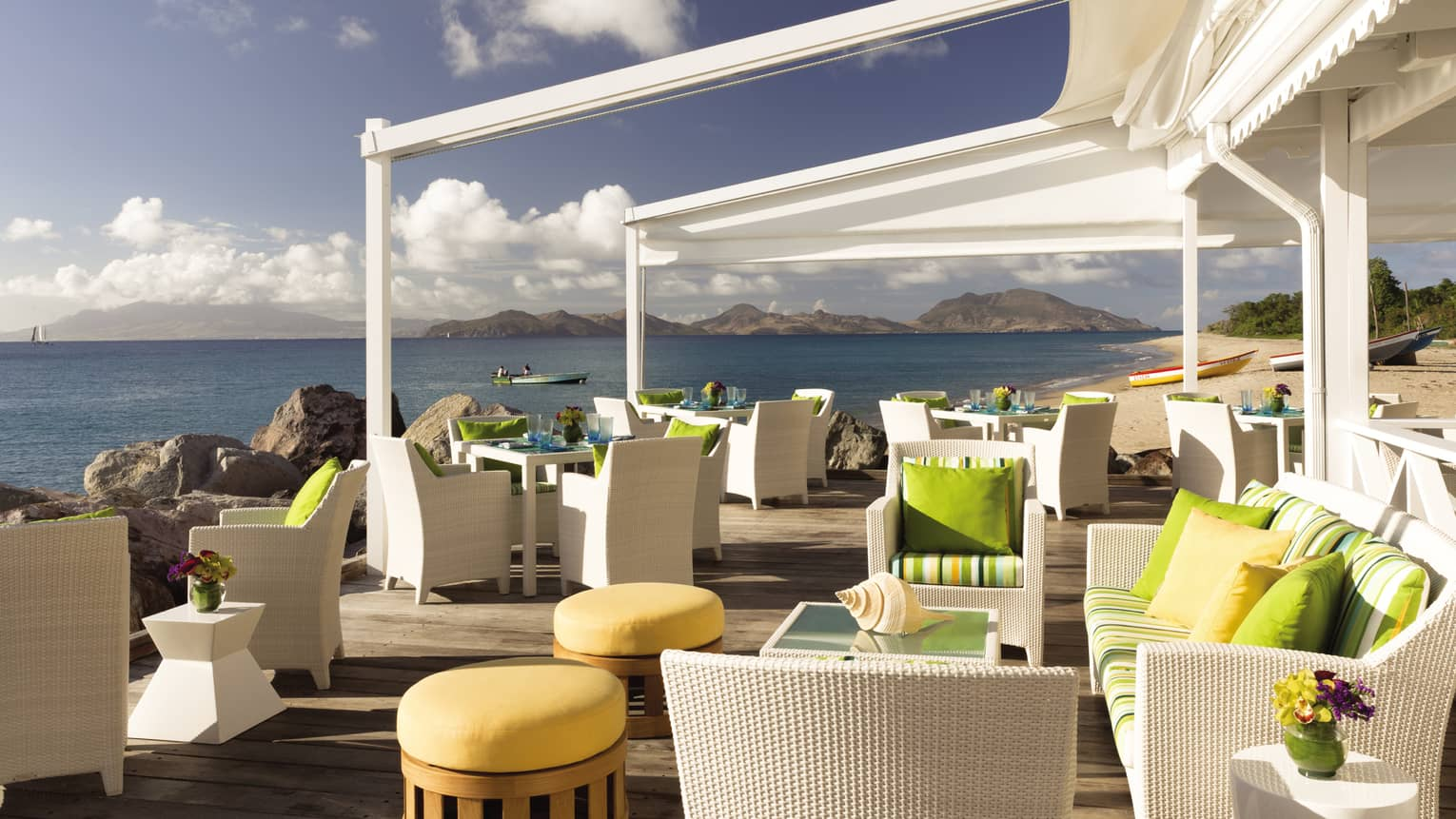 Mango restaurant patio white wicker furniture, yellow stools, deck over ocean